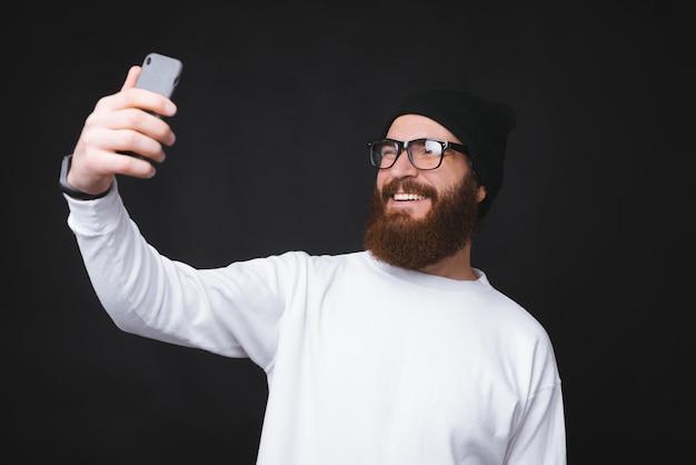Hombre feliz barba hipster tomando selfie sobre fondo oscuro