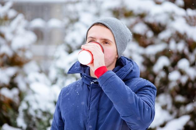 Hombre feliz bebiendo café al aire libre en invierno