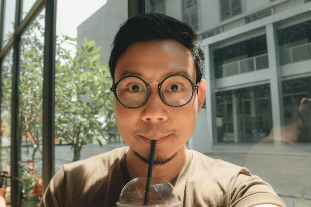 El hombre feliz está bebiendo café con hielo en la cafetería ocultarse del sol brillante.
