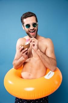 Hombre feliz bebiendo cócteles de coco