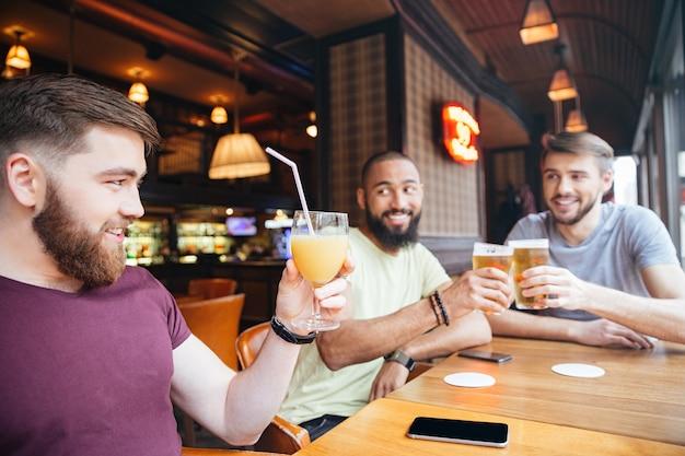 Hombre feliz bebiendo jugo de naranja mientras amigos bebiendo cerveza en el pub