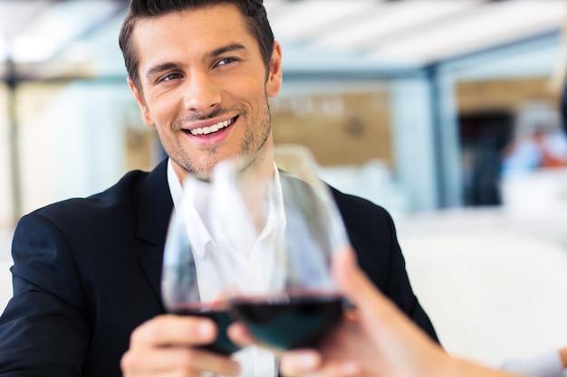 Hombre feliz bebiendo vino en el restaurante