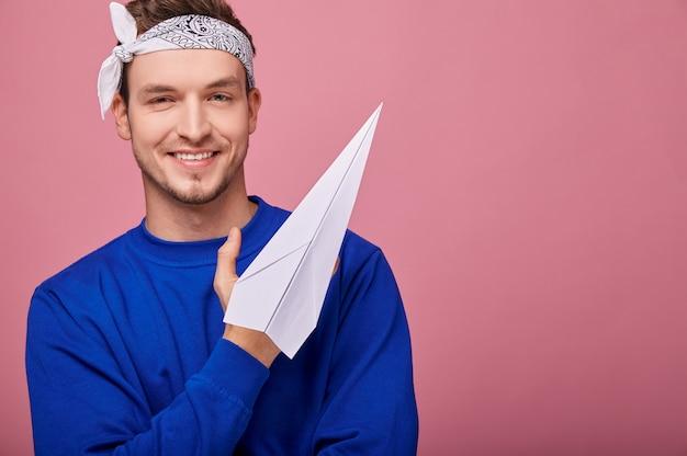 Hombre feliz en blanco con patrones bandanwith avión de papel blanco