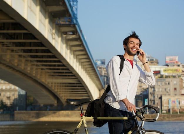 Hombre feliz caminando al aire libre con bicicleta y teléfono móvil