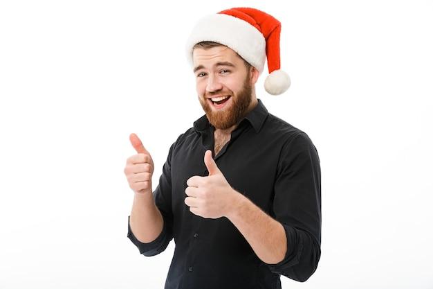 Hombre feliz en camisa y sombrero de navidad mostrando los pulgares para arriba