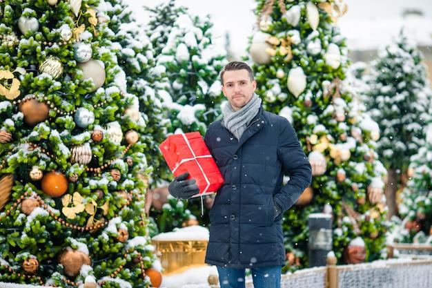 Hombre feliz cerca de la rama de abeto en la nieve para año nuevo.