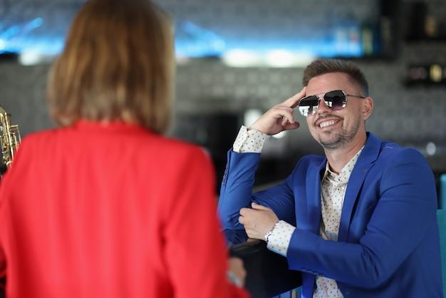 Hombre feliz en chaqueta azul con barba y gafas de sol sentado en el bar con la cabeza en la mano.
