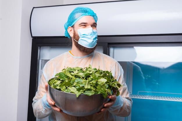 Hombre feliz chef con máscara facial y sosteniendo un tazón grande con espinacas