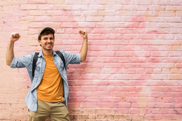 Hombre feliz en la ciudad con pared rosa