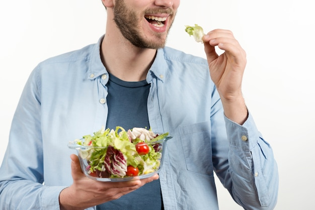 Hombre feliz comiendo ensalada saludable contra fondo blanco