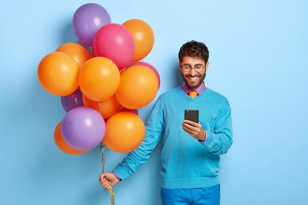 Hombre feliz y complacido recibe un mensaje de felicitación en el teléfono móvil, celebra su salida de la universidad