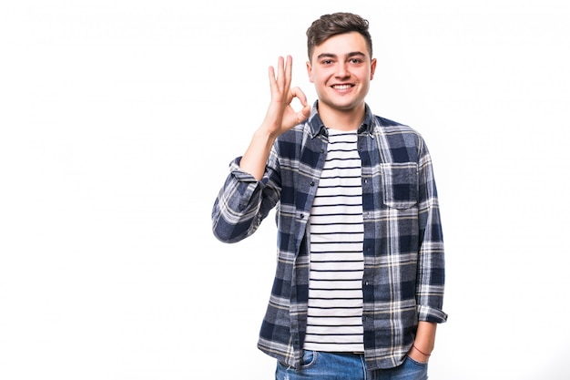 Hombre feliz dando señal bien delante de la pared blanca