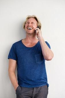 Hombre feliz de pie junto a una pared y hablando por teléfono móvil