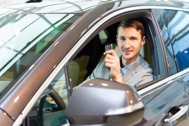 Hombre feliz dentro de auto nuevo