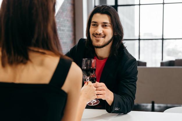 Hombre feliz dice brindis por su amada mujer y sostiene una copa de vino en la mano