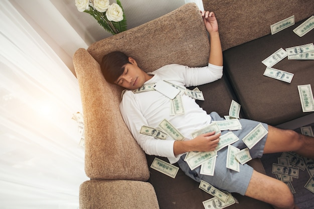 Hombre feliz con dinero en efectivo volando en la oficina en casa, rico del concepto de negocio en línea