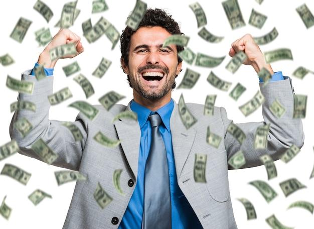 Hombre feliz disfrutando de la lluvia de dinero