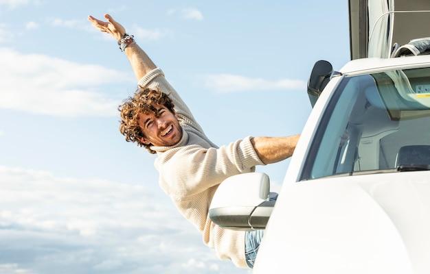 Hombre feliz disfrutando de un viaje por carretera