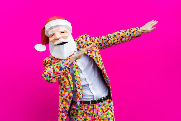 Hombre feliz con divertida máscara de polietileno baja en la pared de color