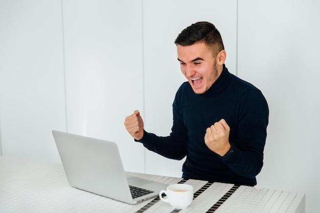El hombre feliz emocionado que muestra los puños, celebra su éxito después de ganar en línea.