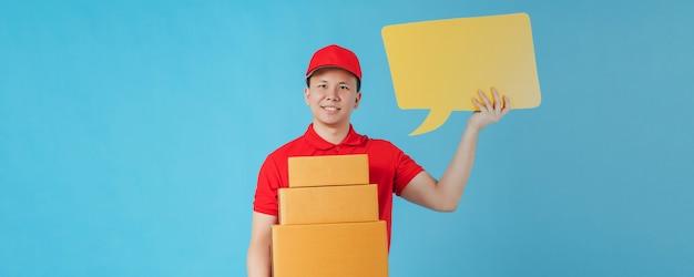 Hombre feliz entrega asiático vistiendo una camisa roja mientras sostiene cajas de paquetes de papel y bocadillo amarillo