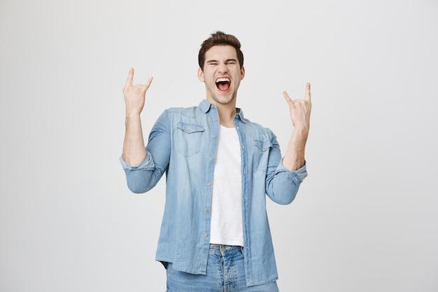 Hombre feliz entusiasta que se divierte, muestra gesto de rock-n-roll