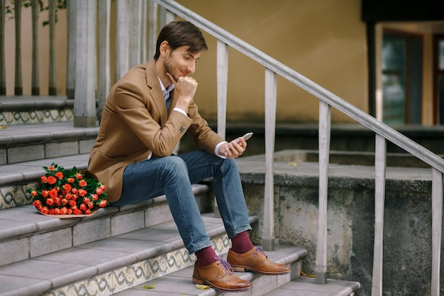Hombre feliz enviando mensajes de texto mientras sonríe