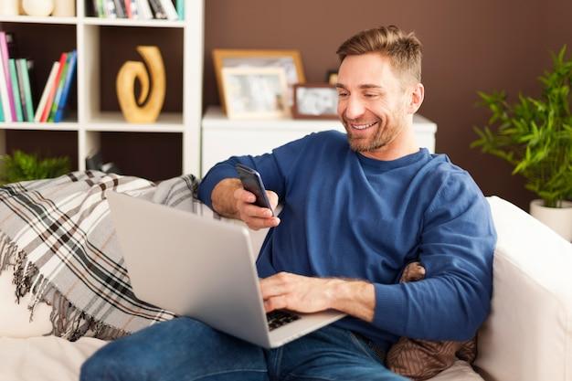 Hombre feliz escaneando el código qr por teléfono móvil en casa