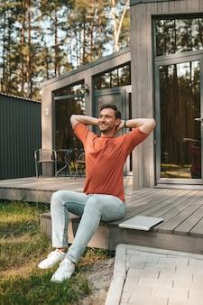 Hombre feliz. feliz sonriente hombre de estiramiento en camiseta y jeans sentado cerca de la computadora portátil en el porche de la casa en la tarde fina