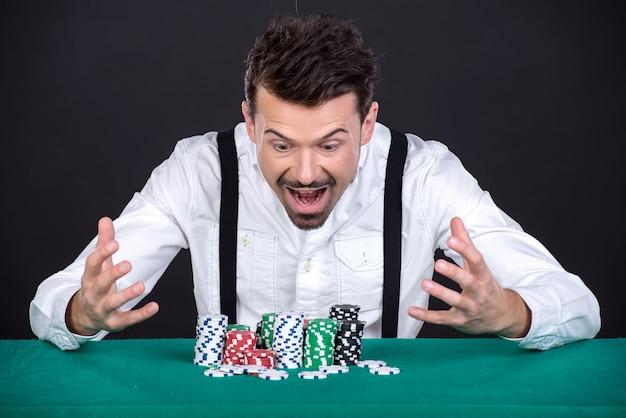 Hombre feliz con fichas en el casino.