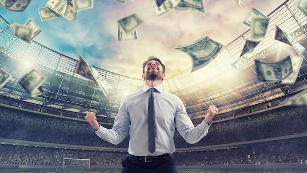 Hombre feliz por ganar una apuesta deportiva lluvia de dinero dentro de un estadio de fútbol