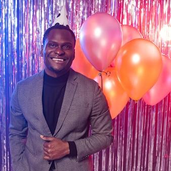 Hombre feliz con globos vista frontal