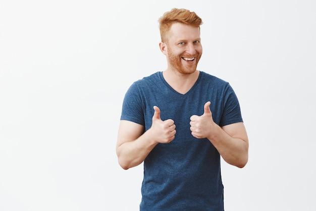 Hombre feliz y guapo complacido con cabello pelirrojo y brislte, mostrando los pulgares hacia arriba y sonriendo ampliamente, dando comentarios positivos, compartiendo su opinión positiva sobre la pared gris