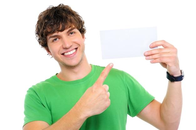 Hombre feliz guapo mostrando con el dedo en la tarjeta en blanco