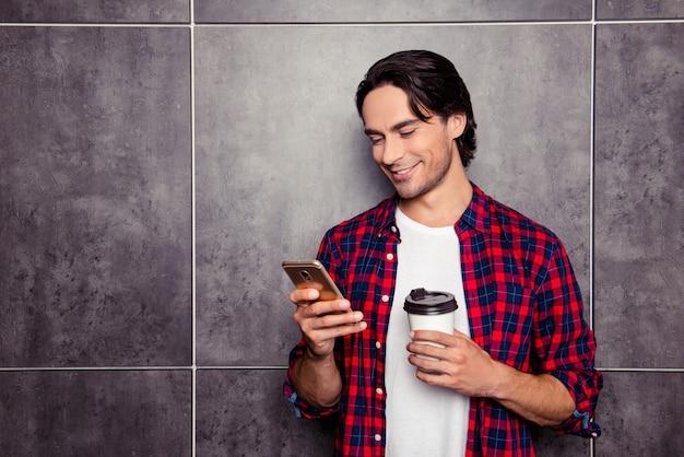 Hombre feliz guapo con taza de café leyendo sms en el teléfono