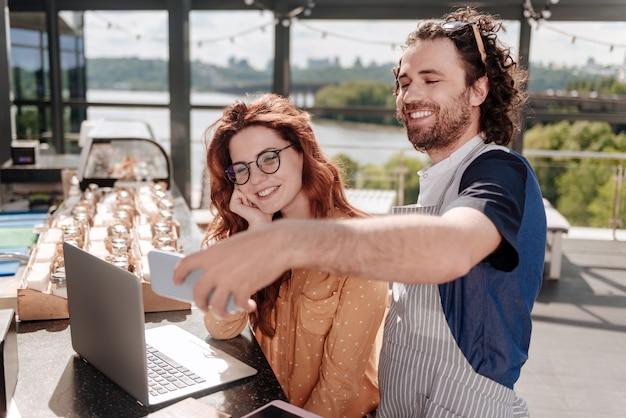 Hombre feliz. hombre feliz barbudo haciendo selfie con su esposa creando un nuevo menú de verano para su terraza de verano