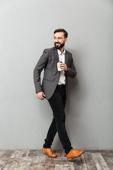 Hombre feliz integral con café para llevar sonriendo y caminando a lo largo de gris