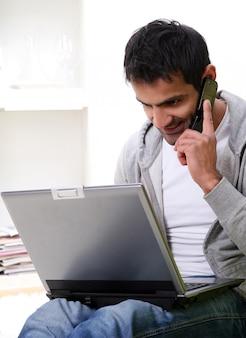 Hombre feliz y joven con laptop y teléfono