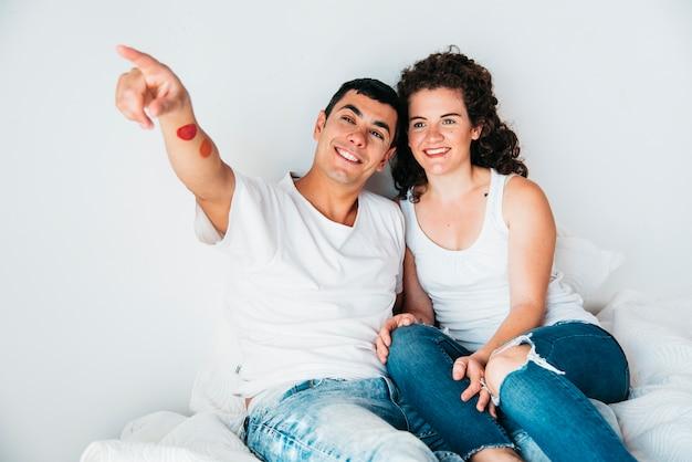 Hombre feliz joven con la mano estirada y la mujer que se sientan en cama