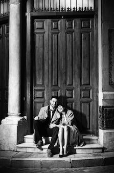 Hombre feliz joven y mujer que se sientan cerca de puerta en la calle