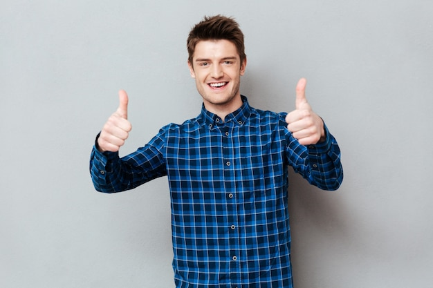 Hombre feliz joven que detiene los pulgares para arriba aislado