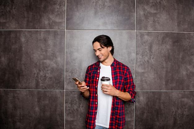 Hombre feliz lee el mensaje en el teléfono y bebe café