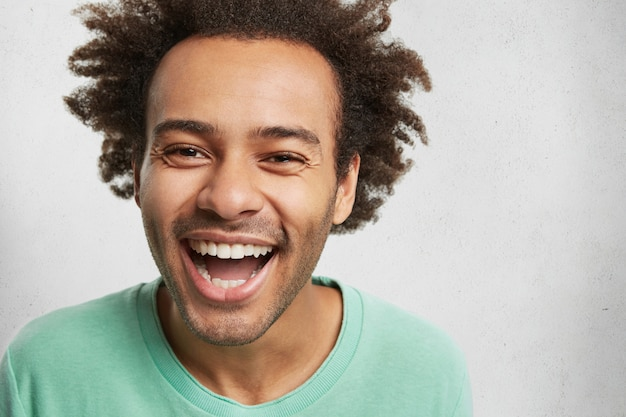 Hombre feliz lleno de alegría con piel oscura y peinado tupido, sonríe a la cámara, expresa emociones positivas