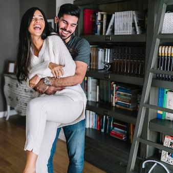 Hombre feliz llevando a su novia en casa