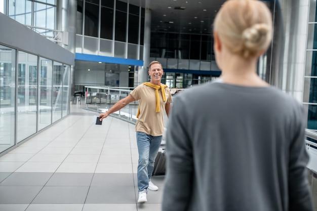 Hombre feliz con maleta caminando hacia la mujer