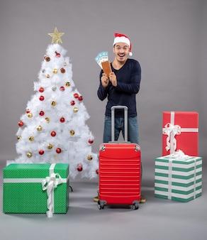 Hombre feliz con maleta roja mostrando sus billetes de viaje en gris