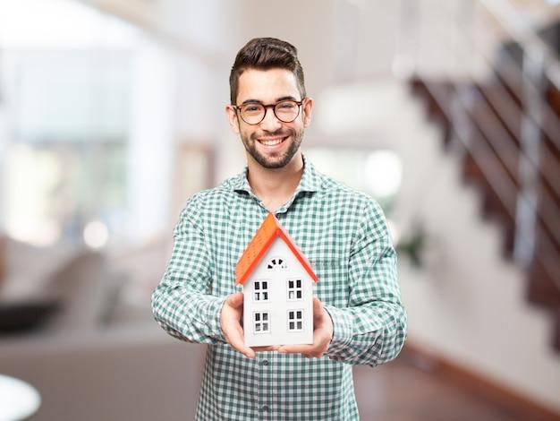 Hombre feliz con la miniatura de su futuro hogar