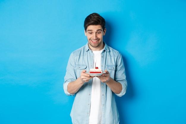Hombre feliz mirando el pastel de cumpleaños y haciendo con, de pie sobre fondo azul.