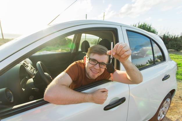 Hombre feliz mostrando la llave de su coche nuevo. concepto de compra y personas de auto
