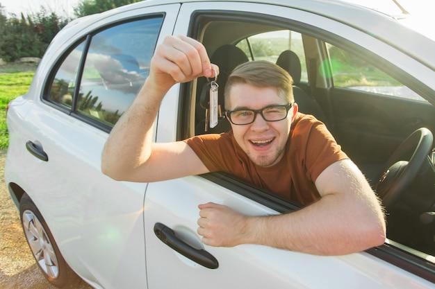 Hombre feliz mostrando la llave de su coche nuevo.